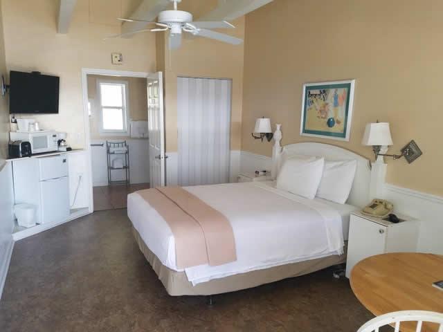 Queen bed in ADA room with view toward bath